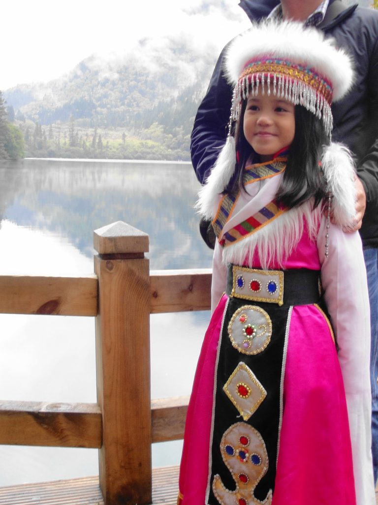 Local girl in traditional dress, Jiuzhaigou National Park Jiuzhaigou National Park, Customer Corner: