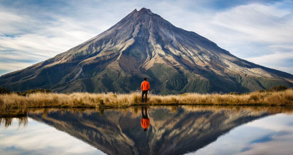 Man standing in front of lake looking at Mt Tarakani in Egmont National Park